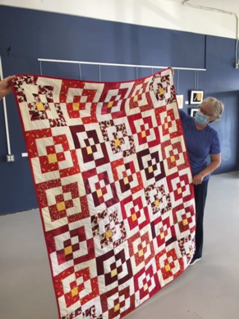 Christine Orr, QoV Rep and EDQG member holding one of the lovely quilts